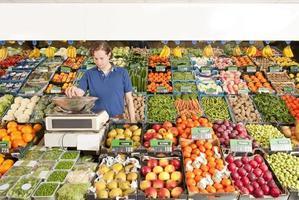 Ein Mann, der in einem grünen Lebensmittelgeschäft arbeitet und Gemüse wiegt foto