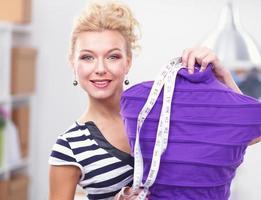 lächelnder Modedesigner, der nahe Mannequin im Büro steht foto