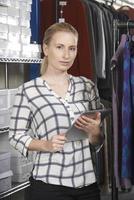Geschäftsfrau läuft online Modegeschäft mit digitalem Tabl foto