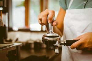 Barista drückt frische Kaffeemühlen foto