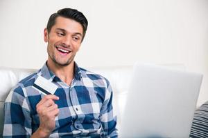 Mann, der Bankkarte hält und Laptop betrachtet foto