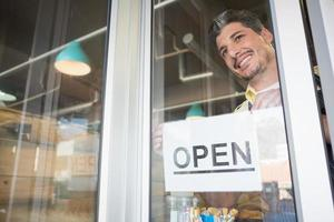 lächelnder Arbeiter, der offenes Zeichen aufstellt foto