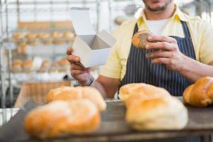 Arbeiter in Schürze mit Kiste und Brot foto