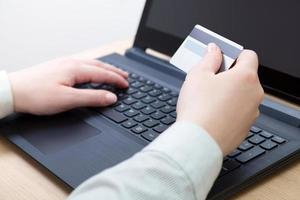 Frau, die online mit Laptop einkauft foto