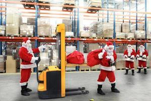Santa Klauseln in der Schlange für die Säcke mit Geschenken foto