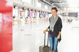 Frau mit einem Koffer im Flughafen foto