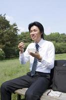 Geschäftsmann, der Lunchpaket isst foto