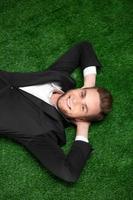 junger Geschäftsmann, der auf grünem Gras liegt foto
