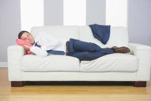 müder attraktiver Geschäftsmann, der auf Couch liegt foto