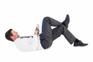 Geschäftsmann liegend und mit Tablette foto