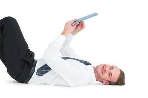 lächelnder Geschäftsmann, der liegt und Tablette benutzt foto