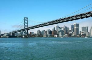 Stadtlandschaft hinter Buchtbrücke in San Francisco über Wasser foto