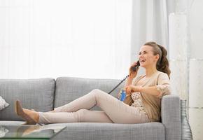 Frau mit Kreditkarte sitzt auf Diwan und spricht Telefon foto