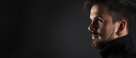 hübscher brutaler Kerl mit Bart auf dunklem Hintergrund foto