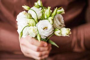 Mann hält Ring und einen Blumenstrauß foto
