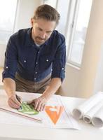 reifer Architekt, der an Blaupause am Schreibtisch arbeitet foto