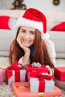 festliche Rothaarige lächelnd an Kamera, die Geschenk hält foto