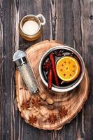Weihnachtsglühgetränk Glühwein mit Gewürzen über Holz foto