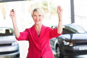 ältere Frau, die ihr neues Auto vom Autohaus abholt foto