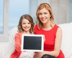 Mutter und Kind halten leere Tablette beim Sitzen hoch
