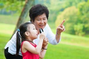 Großmutter und Enkelin zeigen auf etwas im Park foto