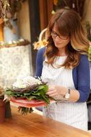 schöne Frau, die im Blumenladen arbeitet foto