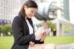 junge weibliche asiatische Geschäftsführerin, die auf Notizblock schreibt foto