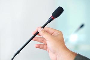 Hand hält Konferenzmikrofon im Besprechungsraum foto