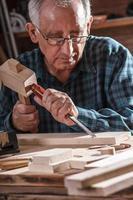leitender Schreiner, der mit Werkzeugen arbeitet. foto