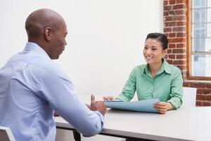 Gelegenheitsgeschäftsleute, die am Schreibtisch sprechen foto