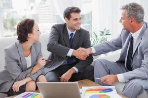 fröhliche Geschäftsleute, die sich auf einen Vertrag einigen
