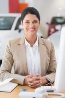 glückliche Geschäftsfrau, die an ihrem Schreibtisch arbeitet foto
