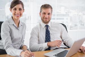 Geschäftsleute, die Kamera mit Laptop lächeln
