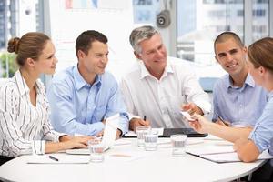 Gruppe von Geschäftsleuten, die in einer Besprechung sitzen foto