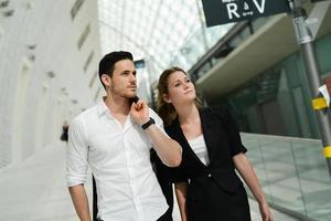 schöne junge Geschäftsleute, die in der öffentlichen Verkehrsstation warten