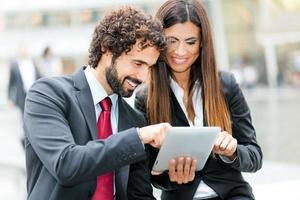 Geschäftsleute, die ein digitales Tablet verwenden foto