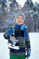 Porträt eines Jungen mit Schlittschuhen, Winter foto