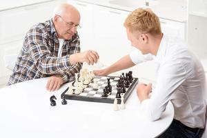 Enkel und Großvater spielen Schach in der Küche