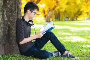 Mann, der Buch im Park liest und unter einem Baum sitzt foto