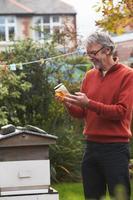 reifer Mann, der Honig betrachtet, der von seinen eigenen Bienen produziert wird foto