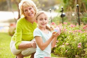 Großmutter mit Enkelin auf Ostereiersuche im Garten foto