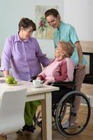 Frau im Rollstuhl, Freundin und Krankenschwester foto