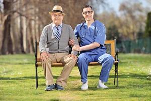 Senior Gentleman und ein Krankenpfleger sitzen auf der Bank foto