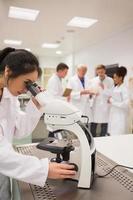 junger Medizinstudent, der mit Mikroskop arbeitet