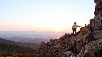 älterer Mann beobachtet Sonnenaufgang über blauem Grat