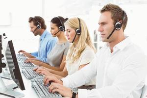 Geschäftsleute mit Headsets, die Computer im Büro verwenden
