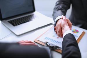 Geschäftsleute, die sich die Hand geben und ein Meeting beenden foto