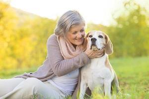 aktive ältere Frau umarmt Hund foto