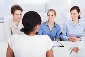 glückliche Geschäftsleute, die im Büro sprechen foto