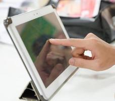 hochauflösende Hand, die digitales Tablet berührt foto